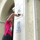 Pia schraubt das go-Schild an das Haus